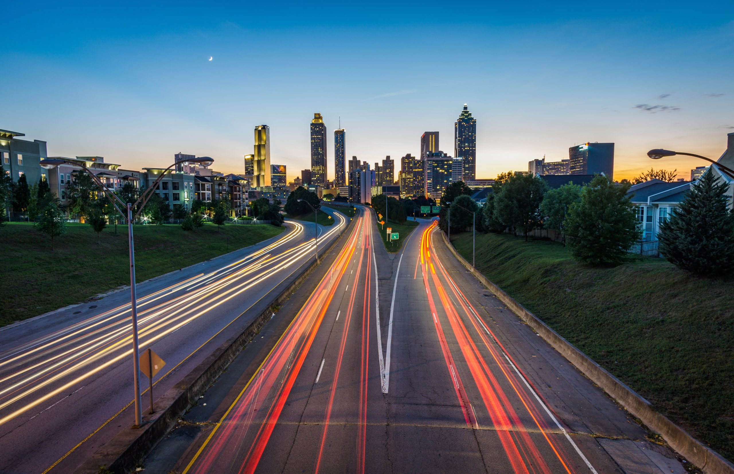 Eine Straße, die auf eine Stadt zuläuft und beleuchtet ist